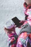Uma menina que guarda um café e um telefone celular imagens de stock