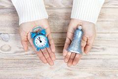 Uma menina que guarda um relógio e um sino O ano novo ou o Natal estão vindo Conceito de ano novo Foto de Stock