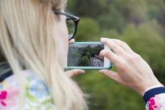 Uma menina que guarda um telefone para fotografar uma opinião da paisagem foto de stock royalty free