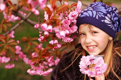 Uma menina que guarda uma árvore de cereja floresce e sorrir Imagens de Stock Royalty Free