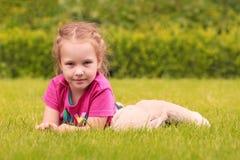 Uma menina que joga com um brinquedo peluches na grama em um parque Imagens de Stock Royalty Free