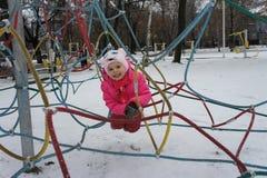 Uma menina que joga em um parque das crianças em um fim de semana do inverno imagem de stock royalty free
