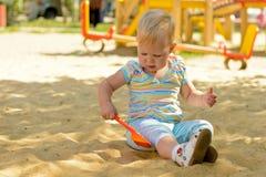 Uma menina que joga na caixa de areia fotografia de stock