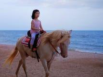 Uma menina que monta um cavalo branco pela praia imagem de stock