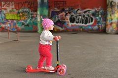Uma menina que monta um 'trotinette' do ` s das crianças em um parque do patim fotografia de stock royalty free