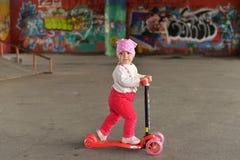 Uma menina que monta um 'trotinette' do ` s das crianças em um parque do patim imagem de stock royalty free