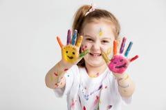 Uma menina que mostra lhe as mãos pintadas coloridas Fotografia de Stock