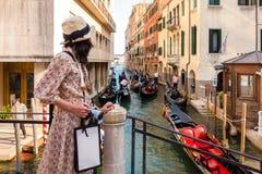 Uma menina que olha as gôndola viajar no canal, Venizia, ele fotografia de stock royalty free