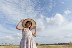Uma menina que que veste um chapéu de palha em um campo no verão Imagens de Stock Royalty Free