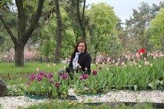 Uma menina que senta-se ao lado das centenas de tulipas vermelhas morena da mulher que senta-se ao lado das tulipas no jardim fotografia de stock royalty free