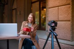 Uma menina que senta-se em um café e que fotografa-se em uma câmera que sorri e que desembala uma caixa de presente outdoors fotos de stock royalty free