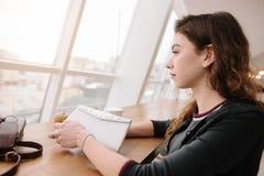 Uma menina que senta-se em um café, olhando para fora a janela foto de stock