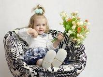 Uma menina que senta-se em uma cadeira com um grupo de flores Imagens de Stock Royalty Free