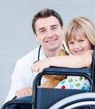 Uma menina que senta-se em uma cadeira de rodas com seu doutor imagens de stock