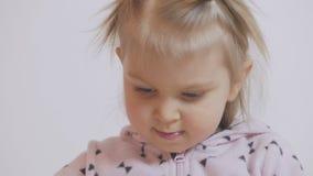 Uma menina que senta-se na concentração da tabela está pintando com a aquarela no papel vídeos de arquivo