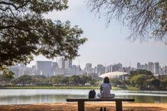 Uma menina que senta-se na frente do lago com a cidade como o backgroung imagens de stock
