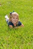 Uma menina que senta-se na grama Foto de Stock Royalty Free