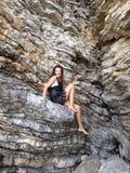 Uma menina que senta-se na rocha foto de stock