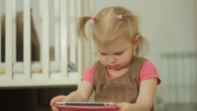 Uma menina que senta-se no assoalho usa um PC da tabuleta, tocando em seu dedo no tela táctil vídeos de arquivo