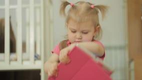 Uma menina que senta-se no assoalho usa um PC da tabuleta, tocando em seu dedo no tela táctil video estoque