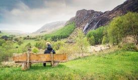 Uma menina que senta-se no banco de madeira e que olha a cachoeira em Kenmare fotografia de stock royalty free