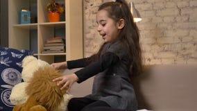 Uma menina que senta-se no sofá e que joga com um urso de peluche e um leão, brinquedos macios, conforto home no fundo filme