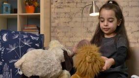 Uma menina que senta-se no sofá e que joga com um urso de peluche e um leão, pentes a pele de um leão do brinquedo, conforto home vídeos de arquivo