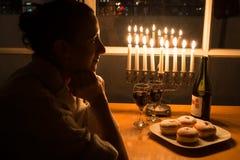 Uma menina que senta-se pela janela com o menorah que comemora o Hanukkah Fotografia de Stock