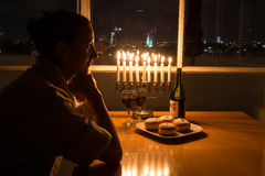 Uma menina que senta-se pela janela com o menorah que comemora o Hanukkah Fotos de Stock