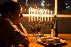 Uma menina que senta-se pela janela com o menorah que comemora o Hanukkah Imagens de Stock