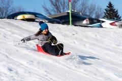 Uma menina que sledging felizmente em Quebeque foto de stock royalty free