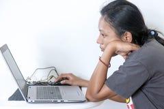 Uma menina que usa o caderno em casa Foto de Stock