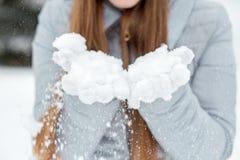 Uma menina que veste o inverno morno veste a neve de sopro na floresta do inverno Fotos de Stock