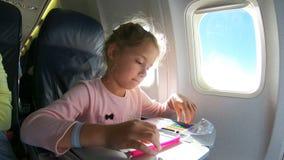 Uma menina que viaja por um avião e que tira uma imagem com lápis coloridos filme