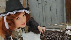 Uma menina ruivo bonita na roupa étnica está estando com uma grande cesta na rua no inverno Há um arquivo de vídeos de arquivo