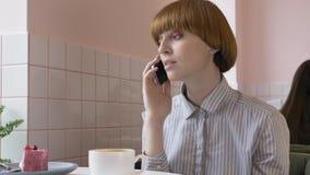 Uma menina ruivo bonita nova está sentando-se em um café, usando um smartphone, respondendo a um telefonema, falando no telefone vídeos de arquivo