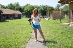 Uma menina ruivo feliz está com uma câmera ao longo de um trajeto em um acampamento, entre casas de verão de madeira, em um dia e foto de stock royalty free