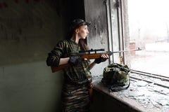 Uma menina ruivo fina est? na janela quebrada com um rifle A menina na camuflagem verde com uma arma Servi?o militar para fotografia de stock royalty free