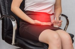Uma menina senta-se em uma cadeira do escritório e guarda-se um comprimido para a dor na menstruação, negócio, close-up, anti-inf foto de stock