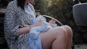 Uma menina senta-se em um banco de parque e balan?a-se o beb? video estoque