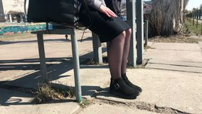 Uma menina senta-se em um banco em uma parada do ?nibus e agita-se seus p?s na antecipa??o vídeos de arquivo