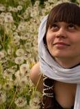 Uma menina senta-se em um campo e em apreciar o verão Fotos de Stock