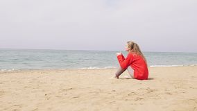 Uma menina senta-se em um Sandy Beach e em olhar o mar vídeos de arquivo