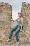 Uma menina senta-se em uma ameia de uma parede de pedra Fotografia de Stock