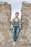 Uma menina senta-se em uma ameia de uma parede de pedra Imagens de Stock Royalty Free