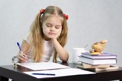 A menina escreve em um pedaço de papel que senta-se na tabela na imagem do escritor Fotografia de Stock Royalty Free