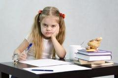 A menina escreve em um pedaço de papel que senta-se na tabela na imagem do escritor Imagens de Stock Royalty Free