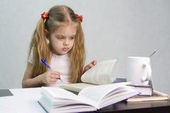 A menina que folheia através do livro e escreveu em uma folha de papel o assento abstrato na tabela Fotos de Stock Royalty Free