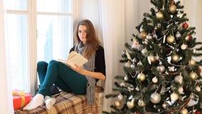 Uma menina senta-se a janela e pela leitura de um ano novo do livro video estoque