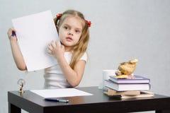A menina mostra a folha de papel com notas scribbled, sentando-se na tabela na imagem do escritor Imagens de Stock